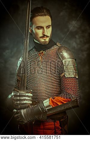 Brave medieval knight with sword and armour on a grunge background.