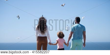 Happy Family On The Beach. People Having Fun On Summer Vacation. Father, Mother And Child On Blue Se