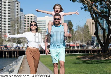 Portrait Of Happy Young Family Walking With Their Child On The City. Joyful Father Giving Piggyback