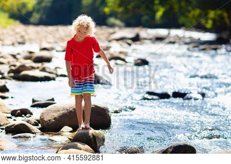 Child Hiking In Mountains. Kids At River Shore.