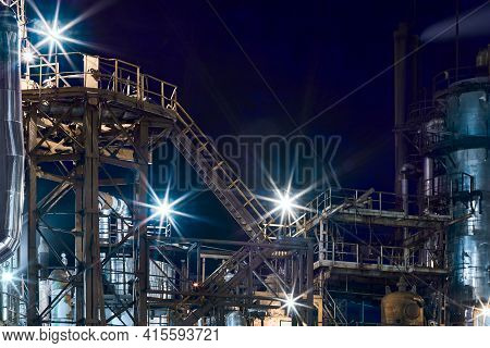 Night Industrial Petrochemical Landscape. Reactors Pipes Stairs And Columns. Large-capacity Producti
