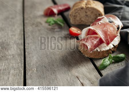 Italian Cuisine Concept. Crusty Bread Toast With Cream Cheese And Thinly Sliced Ham, Cherry Tomatos,