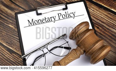 Paper With Monetary Policy With Gavel, Pen And Glasses On Wooden Background