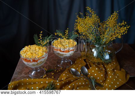 Traditional Russian Salad Mimosa Decorated With Flowering Sprigs Of Mimosa. Puff Salad With Potatoes