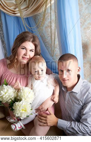 Portrait Of A Little Blonde Girl, Plump Chubby Mother And Big Father. Family In Studio During Photo