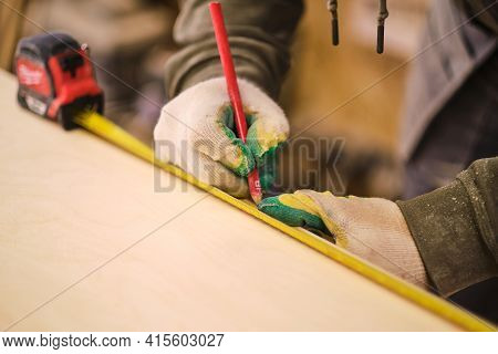 Close Up. Carpenter Holding A Measure Tape On The Work Bench. Woodwork And Furniture Making Concept.