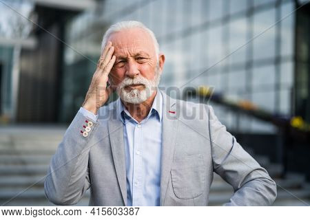Senior Businessman Is Tired Of Work. He Is Standing In Front Of Company Building And Having Headache