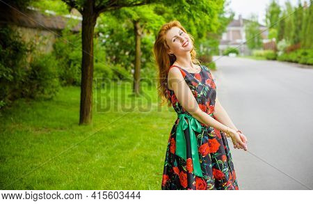 Retro Girl With Red Lips In A Dress With A Print Of Roses On A Beautiful Summer Background. Young Re