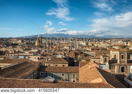 Catania cityscape with the view of Etna volcano at sunset in Sicily, Italy. Catania downtown top view with majestic Etna at background