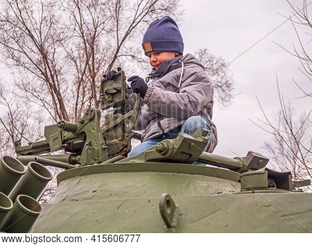 An Eight-year-old Caucasian Boy In A Gray Jacket And A Blue Knitted Hat Sits On A Tank Turret And Is