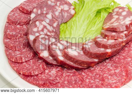 Slices Of Dry-cured And Smoked Sausages On Dish, Fragment Close-up In Selective Focus