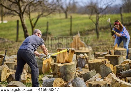 A Man And Woman Splitting Large Beech Wood.