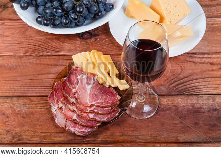 Sliced Dry-cured Pork Neck And Cheese, Glass Of Red Wine On An Old Rustic Table, Top View