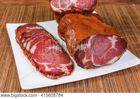 Partly Sliced Dry-cured Pork Neck On The Square White Dish On Bamboo Table Mat, Close-up In Selectiv