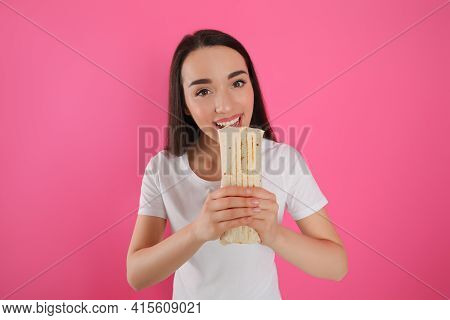 Young Woman Eating Tasty Shawarma On Pink Background