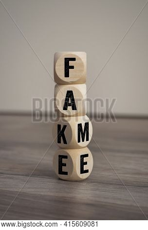 Tower Made With Cubes, Dice Or Blocks With The Words Fake And Fame On Wooden Background