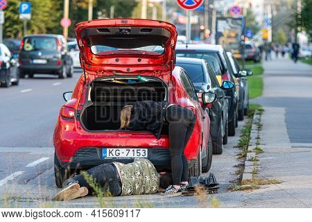 Riga, Latvia - September 30, 2020: Man And Woman Repairing A Car That Parked On The Roadside