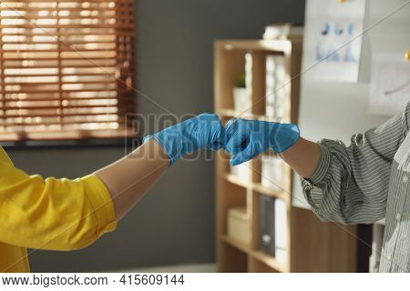People Greeting Each Other By Bumping Fists Instead Of Handshake Indoors, Closeup