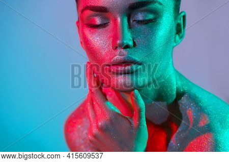High Fashion model woman in colorful bright silver sparkles and neon lights posing in studio, portrait of beautiful girl, trendy glowing sequins make-up. Art design make up. Glitter Vivid makeup