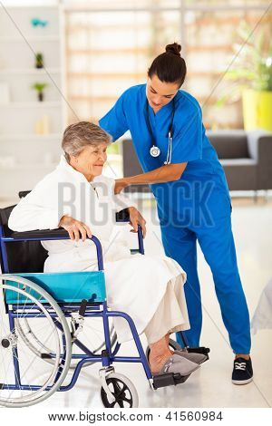 friendly caregiver helping senior woman on wheelchair