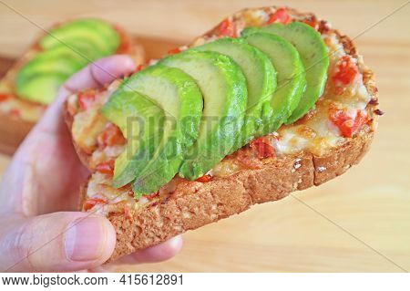 Closeup Hand Holding A Delectable Grilled Cheese Toast With Tomato And Sliced Fresh Avocado