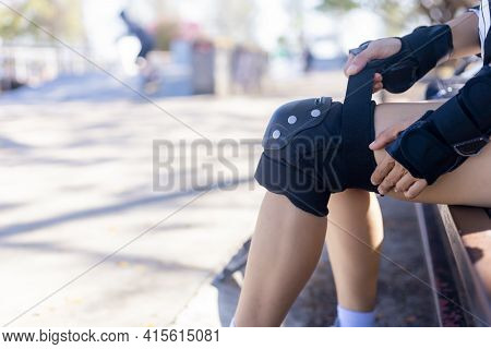 Close Up Woman Surf Skate Board Putting On Knee Protector Pads On Her Arm And Wearing Wrist Guards.