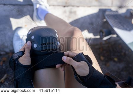 Top View Close Up Woman Surf Skate Board Putting On Knee Protector Pads On Her Arm And Wearing Wrist