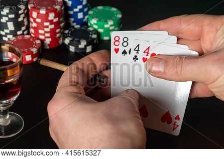 Poker Cards Two Pairs Combination. Close Up Of A Gambler Hand Is Holding Playing Cards And Sigar In