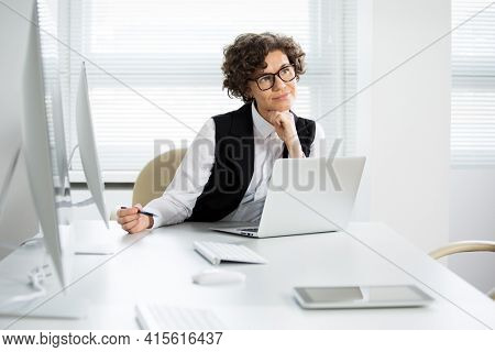 Portrait of a pretty business woman woman with glasses at workplace in office