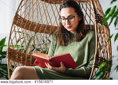 Woman Relaxing At Home. Woman Relaxing With Book At Home. Domestic Lifestyle. Woman At Home. Lifesty