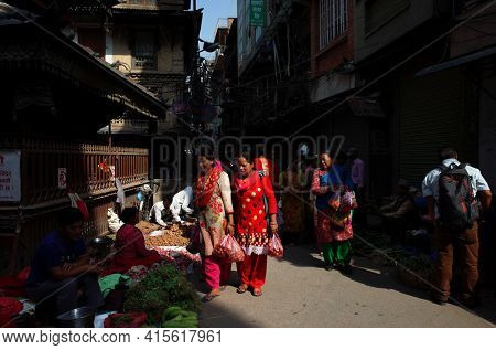Kathmandu, Nepal - June 17, 2019: Local daily life on street, Two nepali women in traditional red clothes shopping on street market on crowded narrow street in old town