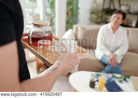 Cropped Image Of Caring Son Bringing Tray With Pot Of Tea And Sugar To His Mature Mother Resting On