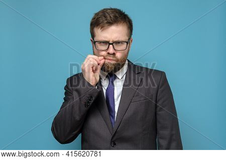 Caucasian Man In Business Suit, Sternly And Looks, Touching Mustache With Hands. Blue Background.