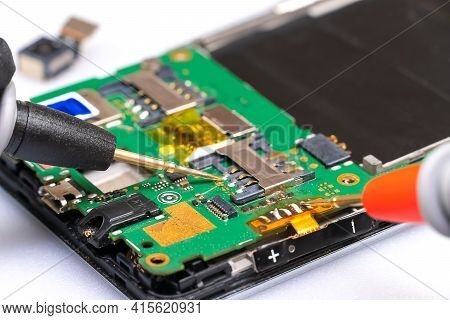 Master Of Radio Engineering Repairs A Part Of The Mobile Phone, Making Measurements On It With A Dig