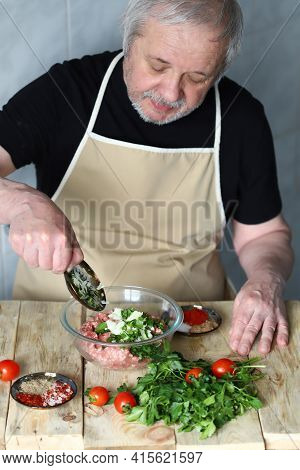 Man Chef Loads Spices Into A Bowl Of Minced Meat. Cooking Minced Meat For Cutlets, Hamburger Or Keba