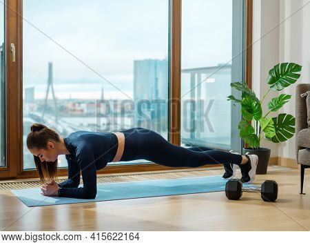 Slender brunette with ponytail in green tracksuit does exercise in plank pose on blue mat by panoramic window with street outside