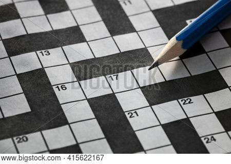 Solving a crossword puzzle with blue pencil background
