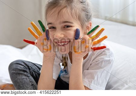 Cheerful Little Girl With Palms Painted With Smiles. Children's Creativity And Art.