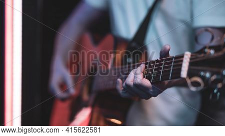 A Man Plays An Acoustic Guitar In A Dark Room. Live Performance, Acoustic Concert.