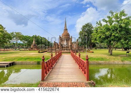 Red Wooden Bridge Across The Pond Leading To Pagoda And Ruined Chapel Monastery Complex At Wat Sa Si