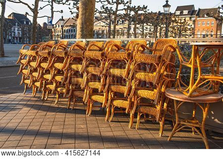 Outdoor Furniture On A Cafe Terrace, Stacked Wicker Chairs.  The Beginning Of The Tourist Season. Ne