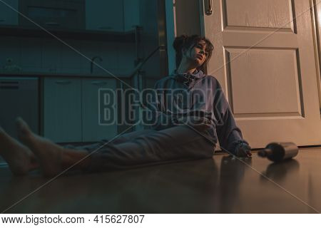 Depressed Young Woman Sitting On The Floor In The Dark, Upset And Desperate, Drunk And Overdosed Wit