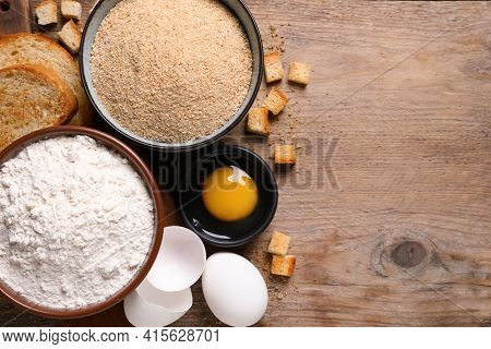Fresh Breadcrumbs, Flour And Eggs On Wooden Table, Flat Lay. Space For Text