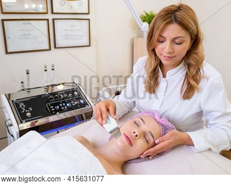 Woman in a spa salon on cosmetic procedures for facial care. Beautician makes medical procedures using a professional  equipment. Cosmetologist making a woman a therapeutic procedure on a face.
