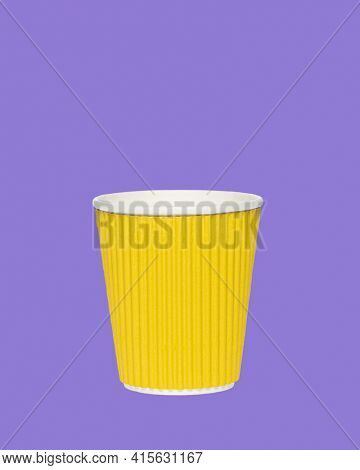 Photo of an yellow paper cup on a colored purple background. Photo of a coffee cup made of recyclable materials. Empty paper coffee cup.