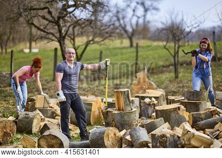 A Family Working Together To Prepare Firewood For The Winter