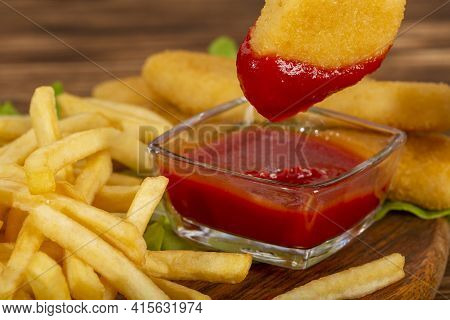 Juicy Chicken Nuggets Are Dipped In Ketchup. Nuggets And French Fries On A Wooden Background.