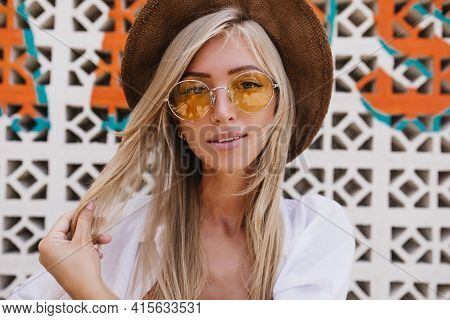 Close-up Portrait Of Charming European Girl Posing At Resort With Gently Smile. Amazing Fair-haired