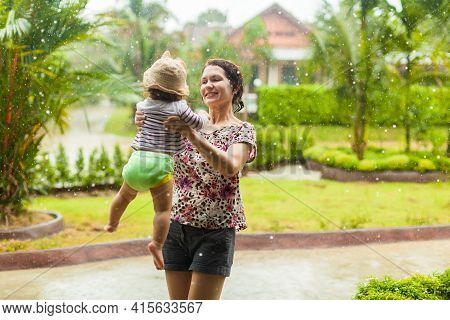 Happy Smiling Family Under Summer Rain. Mother And Little Child Girl Have Fun Time While Playing Out