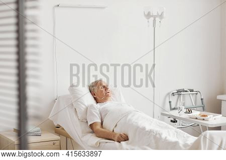 Portrait Of Senior Man Lying On Bed In White Hospital Room With Iv Drip And Oxygen Support, Copy Spa